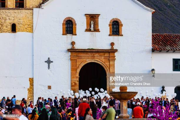 colombia, south america - wedding at the church on the plaza mayor of the historic 16th century town of villa de leyva; white balloons are about to be released in celebration - church wedding decorations stock pictures, royalty-free photos & images