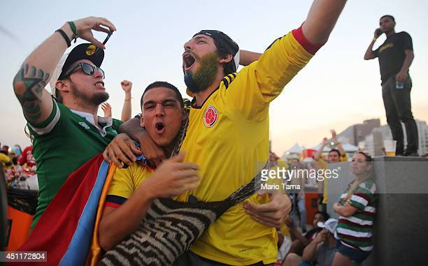 Colombia supporters celebrate after their first goal against Japan while watching at the FIFA Fan Fest on Copacabana Beach on June 24 2014 in Rio de...