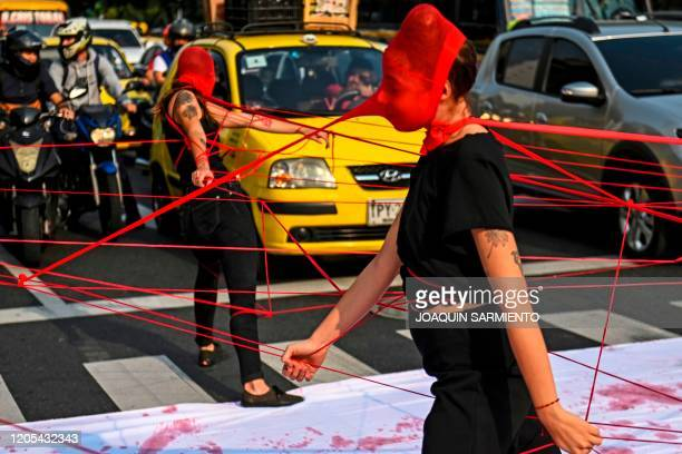 Colombian activists perform during a protest against violence towards women, on a street in Medellin, Colombia, on March 6, 2020.