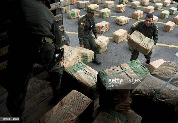 Colombian antidrugs police officer up load packages of marijuana seized in the municipality of Tulua during a news conference in Cali Colombia on...