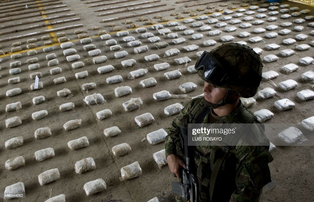 A Colombian Army soldier stands next to packages of seized cocaine during a press conference at a Military Base in Bahia Solano, department of Choco, Colombia, on March 14, 2015. A joint operation between Colombia's Army and Air Force, intercepted a boat near the municipality of Nuqui, west of the country, with 583 kilos of cocaine which, according to authorities, belonged to the criminal gang 'Clan Usuga' and was going to be sent to Central America.