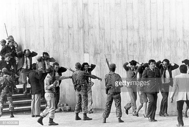 Colombian army troopers protect a group of justices coming out of the Palace of Justice in Bogota occupied 06 November 1985 by a M19 movement...