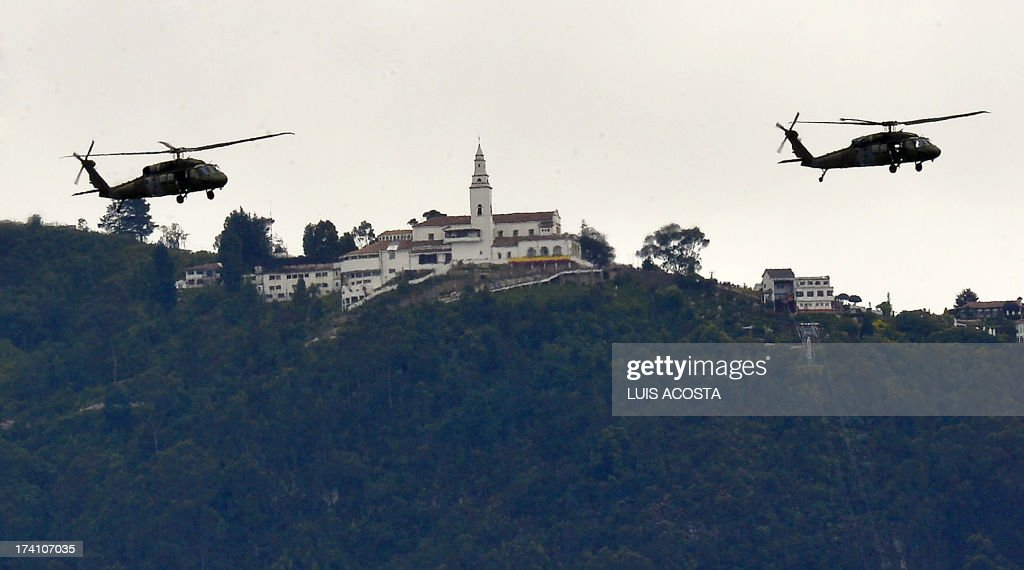 Colombian Black Hawk military helicopters fly in front of Monserrat mount during Independence Day celebrations in Bogota, on July 20, 2012. AFP PHOTO/Luis Acosta /