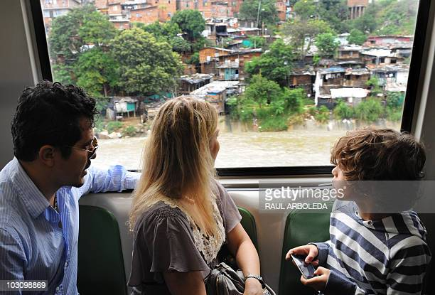 Colombian born actor John Leguizamo his wife Justine Maurer and their son Lucas watch from a window during a visit to Santo Domingo commune on July...