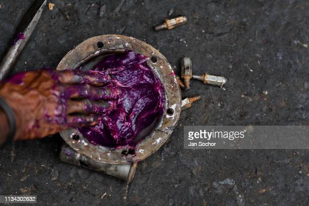 Colombian car mechanic applies the lubricant grease on a truck axle cap during the maintenance service in Barrio Triste on April 18 2018 in Medellin...