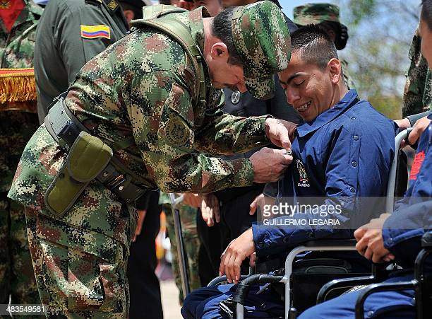 Colombian Chief of Joint Staff of the Armed Forces General Javier Alberto Florez decorates a soldier victim of a landmine during a military ceremony...