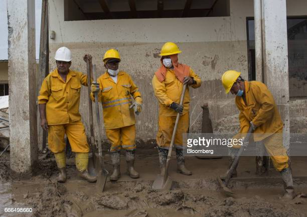 Colombian Civil Defense workers shovel mud outside of a destroyed home after a landslide in the Prospero neighborhood of Mocoa Putumayo Colombia on...