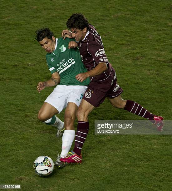 Colombian Deportivo Cali's forward Robin Ramirez vies for the ball with Argentina's Lanus defender Carlos Luciano Araujo during their Libertadores...