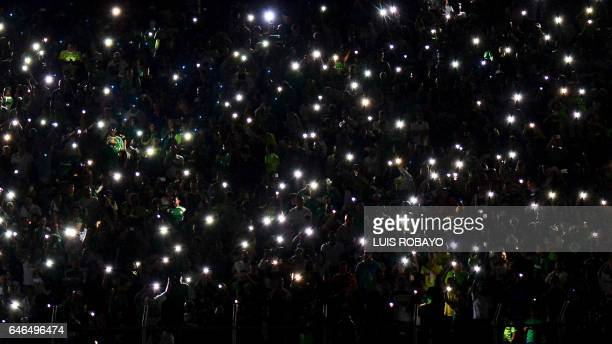 Colombian Deportivo Calis supporters turn on the lights of their mobile phones during a blackout during the Sudamericana Cup match between Colombia's...