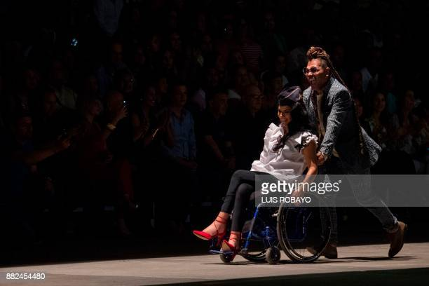 Colombian designer Guio Di Colombia drive a woman in her wheelchair during the Walkway Inclusion fashion show in Cali Colombia on November 29 2017...