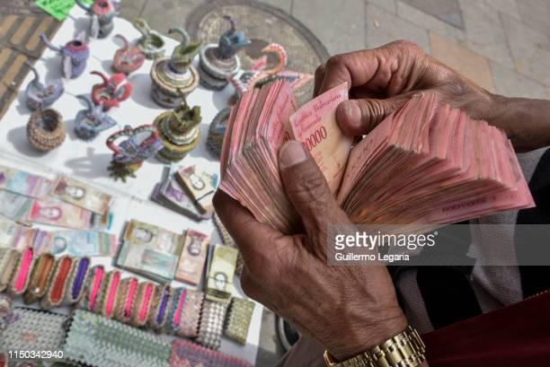 Colombian designer Luis Orlando Ortega counts Venezuelan devalued and out of circulation banknotes Bolivares Fuertes at the main avenue of historic...