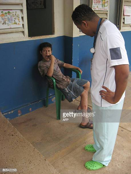 Colombian doctor Daniel Perea looks at a boy who stays on April 5, 2008 at the entrance of a health care centre where Colombian-French Ingrid...