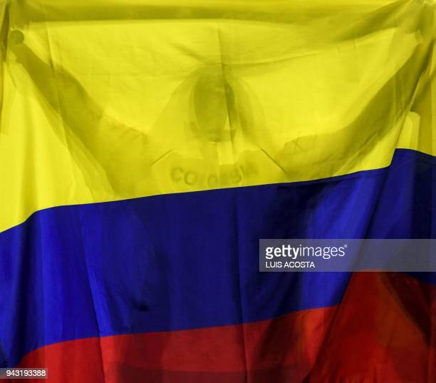 A Colombian fan holds the national flag after countryman Alejandro Gonzalez won against Brazilian tennis player Joao Sorgi in their Americas Zone...
