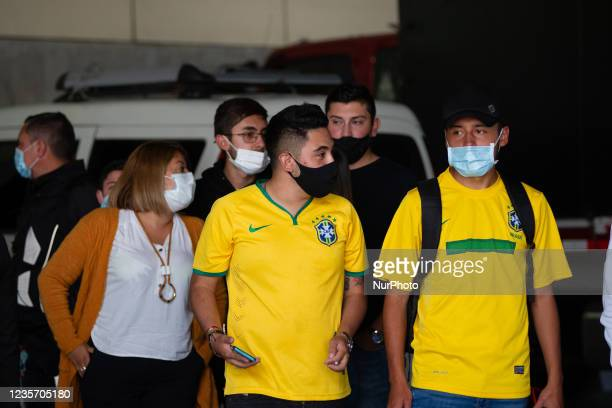 Colombian fans using Brazil's national team t-shirt wait outside for players as members of the Brazil federation of football team board their bus at...