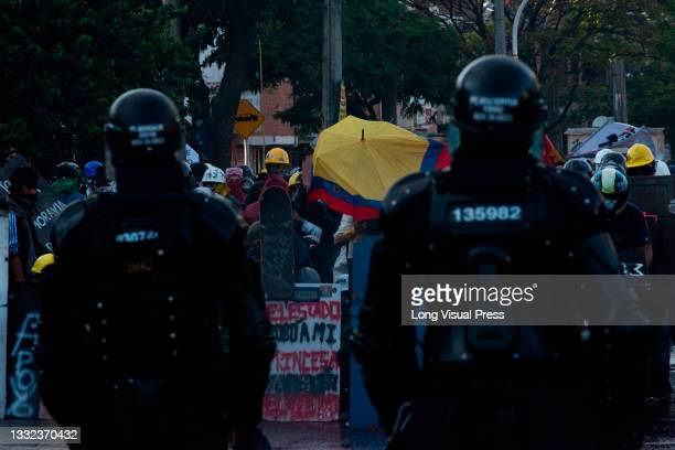Colombian flag parachute is seen in the middle of two riot police officers as they stand as demonstrators prepare to clash as demonstrations ended in...