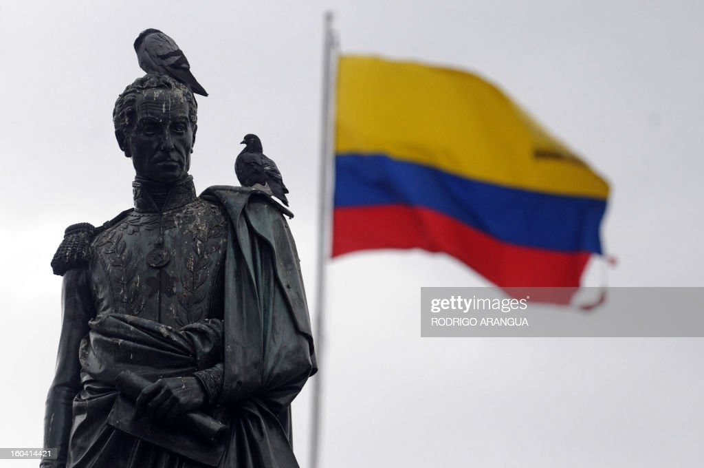 A Colombian flag wabes behind a staute of South American independece hero Simon Bolivar in Bogota on February 9, 2010. AFP PHOTO/Rodrigo ARANGUA /
