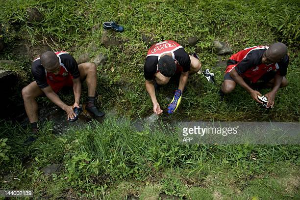 Colombian footballers Jorge Lopez David Holguin and Julio Tobar wash their boots at the end of a training session in Cali Valle del Cauca department...