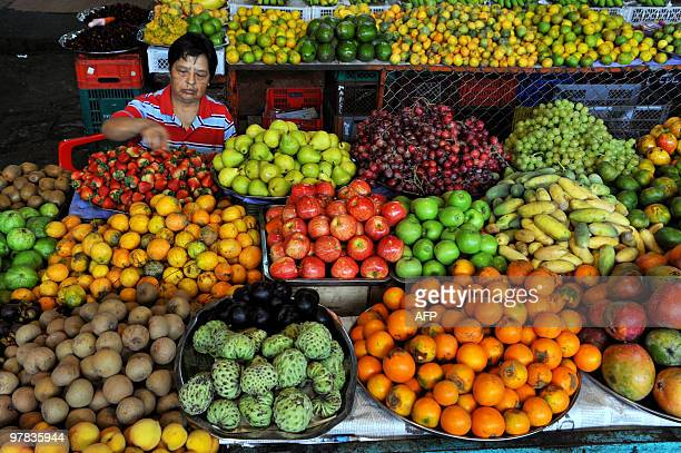 A Colombian fruit vendor arranges strawberries at her stall in La Alameda market on March 18 in Cali Valle del Cauca department Colombia AFP...