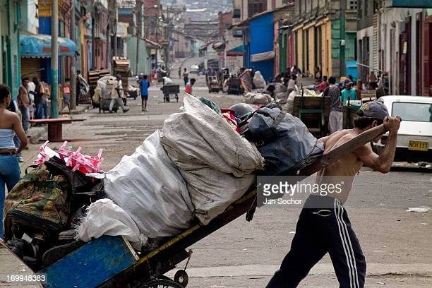 Colombian garbage recollector pulls his fully loaded cart on the street in the slum of Calvario on 5 April 2004 in Cali Colombia Calvario a slum...