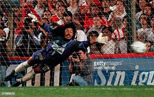 Colombian goalie Rene Higita dives attempting to stop a penalty kick from Argentina's Gustavo Lopez which scored the first goal of the quarter final...