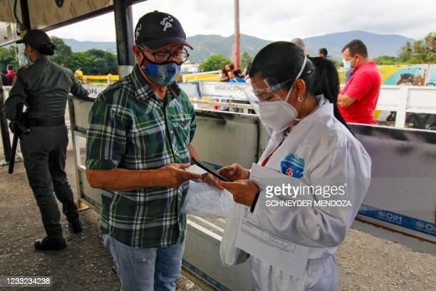 Colombian health worker checks information of a Venezuelan man entering the country following the reopening of the Simon Bolivar International Bridge...