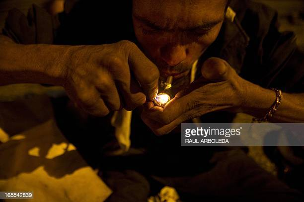 A Colombian homeless man smokes crack in the Barrio Triste neighborhood in Medellin Antioquia department Colombia on April 3 2013 Medellin Mayor's...