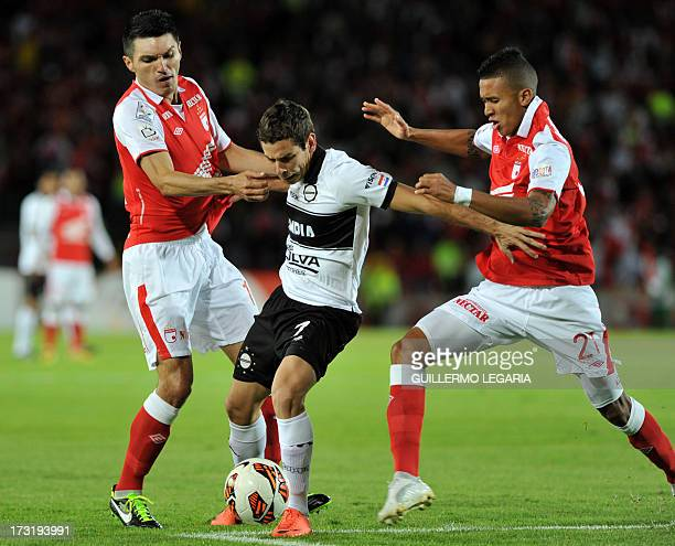Colombian Independiente Santa Fe's players Daniel Torres and Francisco Meza vie for the ball with Enzo Prono of Paraguay's Olimpia during their 2013...