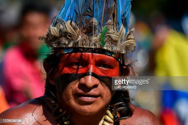 """Colombian indigenous man taking part in a """"Minga"""" walks along the Pan-American highway as he alongside others arrive in the city of Cali with the..."""