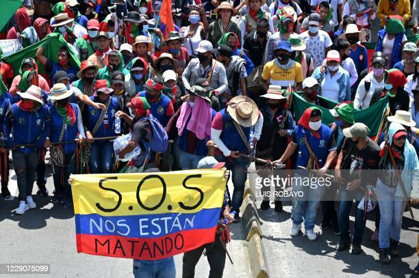 """Colombian indigenous people taking part in a """"Minga"""" march with a Colombian flag reading S.O.S. They are killing us, in Cali, Colombia, on October..."""