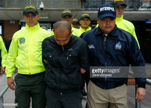 Colombian Juan Carlos Sanchez accused of raping some 276 minors is escorted by Interpol agents and police officers upon leaving an audience in Bogota...