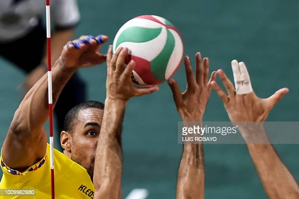 Colombian Liberman Agamez spikes the ball against Puerto Rican Sequiel Sanchez and Jessie Colon in the Men's Volleyball final match during the 2018...