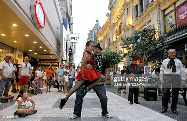 A Colombian male tourist poses for a picture with an Argentinian professional tango dancer at Florida street in Buenos Aires downtown 21 January 2008...