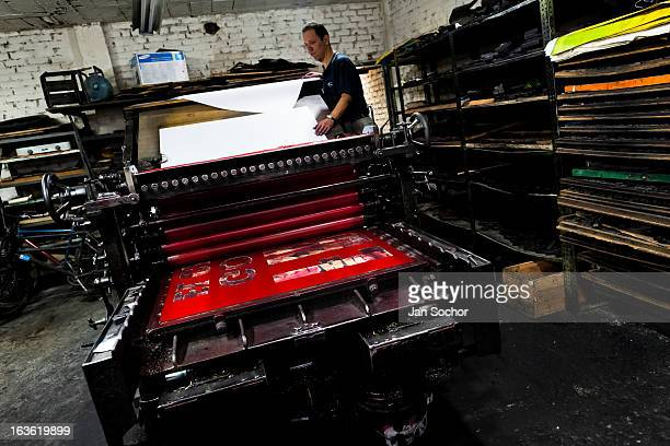 Colombian master printer works on the ancient letterpress machine in the print shop on 1 June 2012 in Cali Colombia Letterpress printing invented by...