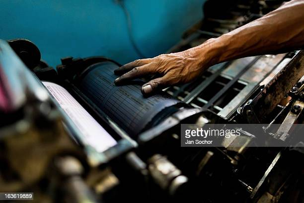 Colombian master printer works on the letterpress machine in the print shop on 2 June 2012 in Cali Colombia Letterpress printing invented by Johannes...