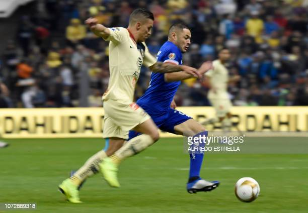 Colombian Mateus Uribe of America challenges Paraguayan Cesar Aguilar of Cruz Azul during the first round match of the final of the Mexican Apertura...