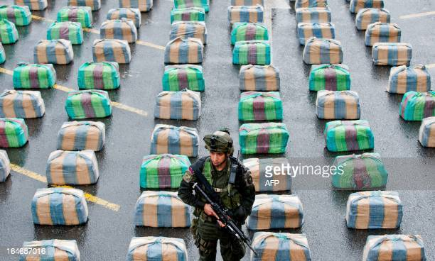 A Colombian member of a police antidrugs unit stands guard next to marijuana packages displayed to the press on March 26 in Cali department of Valle...