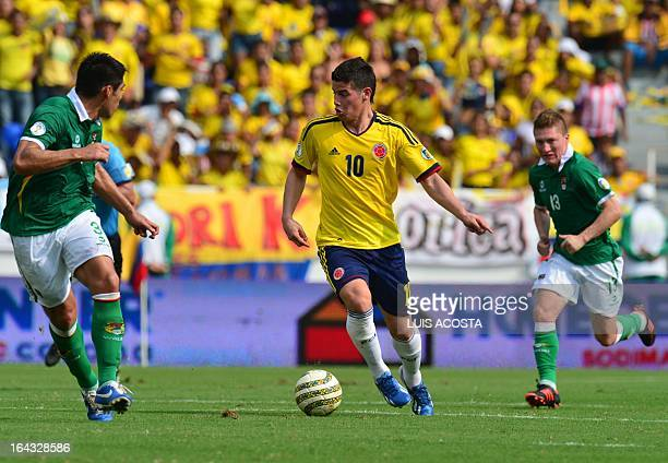 Colombian midfielder James Rodriguez is marked by Bolivian defender Luis Gutierrez and midfielder Alejandro Chumacero during their Brazil 2014 World...