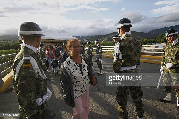 Colombian military police officers stand guard as Venezuelans cross the Simon Bolivar bridge into Cucuta Colombia on Sunday July 17 2016 For only the...
