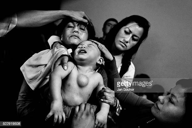 Colombian mother holds her baby boy having a tumor in his chest during the religious healing ritual performed at a house church on January 28 2013 in...