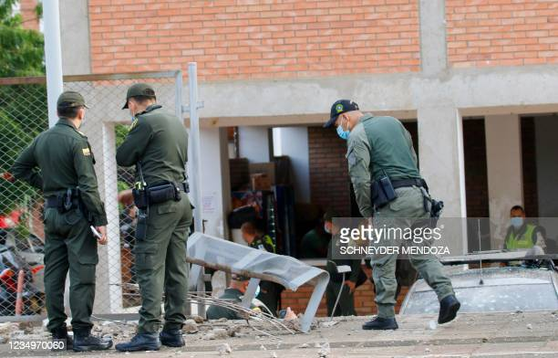 Colombian National Police members look at a police station's facade after an attack with explosives in Cucuta, Colombia, near the border with...