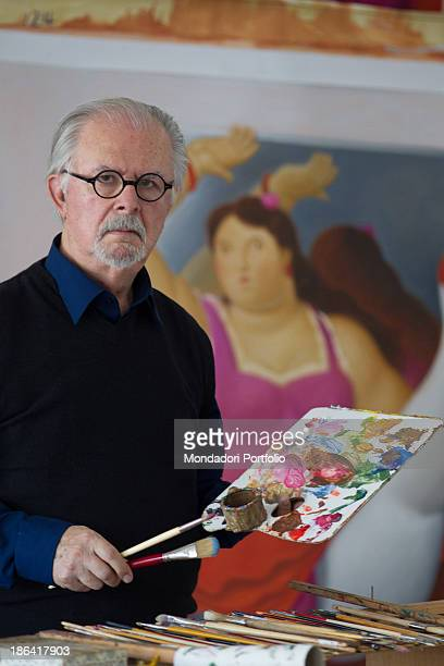 Colombian painter and sculptor Fernando Botero posing in his studio with paint brushes and palette in the hands Behind him a painting depicting a...