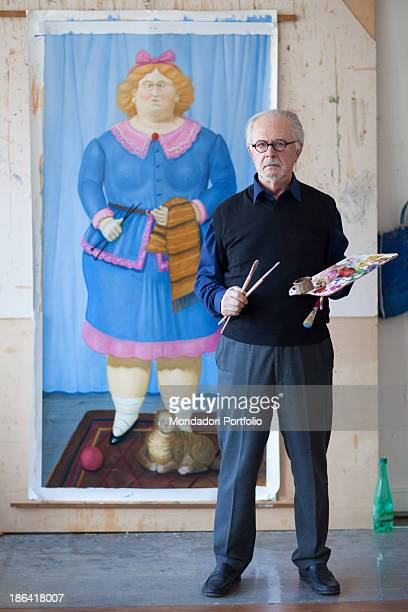 Colombian painter and sculptor Fernando Botero posing with paint brushes and palette in the hands in front of a painting depicting a female figure...
