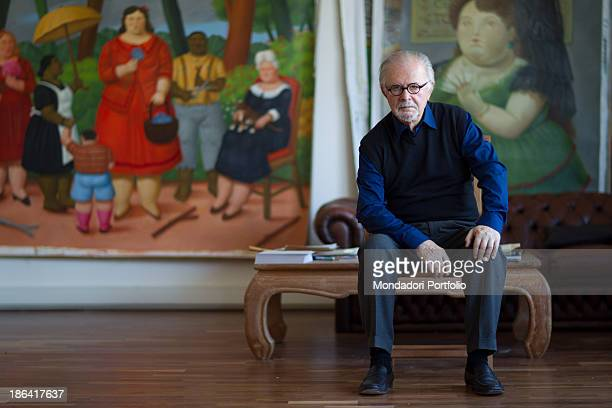 Colombian painter and sculptor Fernando Botero sitting in his studio in front of a some paintings The one on the left portrays a group in a garden...