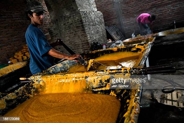 Colombian peasant mixes a hot mass of sugar cane juice during the processing of panela in a rural sugar cane mill in Santa Ana, Valle del Cauca,...