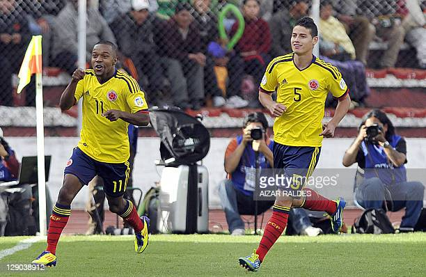 Colombian player Dorlan Pabon celebrates with teammate James Rodriguez after scoring against Bolivia during the Brazil 2014 FIFA World Cup South...