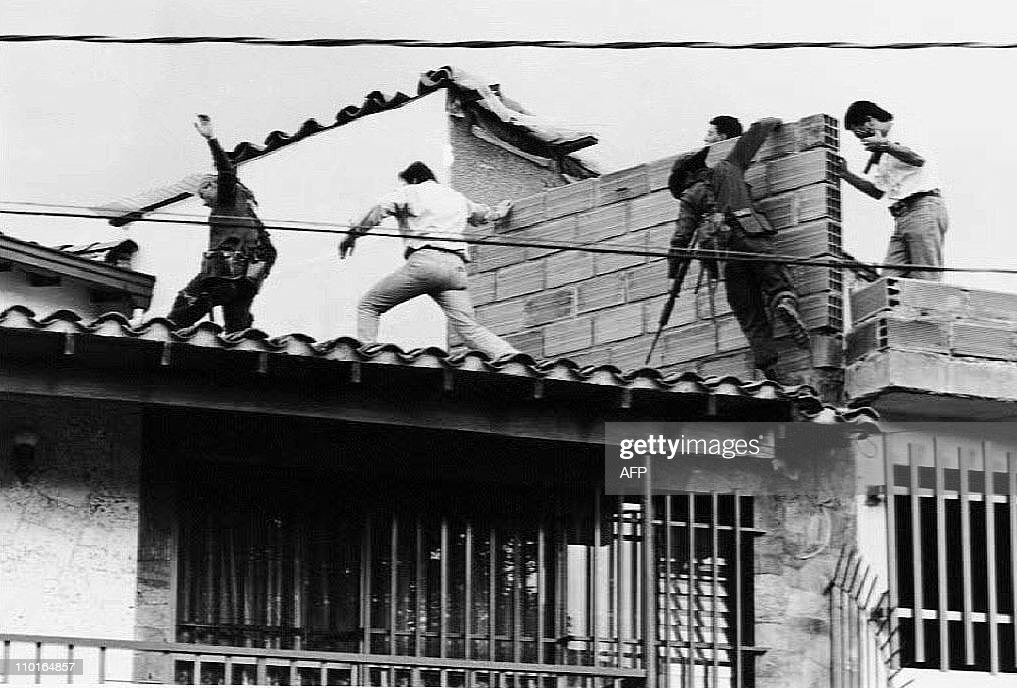 Colombian police and military forces storm the rooftop where drug lord Pablo Escobar was shot dead just moments earlier during an exchange of gunfire between security forces and Escobar and his bodyguard 02 December 1993. The death of Escobar and the bodygaurd ends a 16-month hunt for Escobar, who controlled one of the world's most ruthless drug trafficking empires.