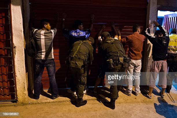 Colombian police frisk a group of men in the Siloe neighborhood during a raid on April 12 2013 in Cali Valle del Cauca department Colombia The...