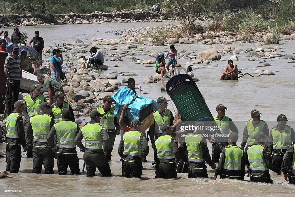 Colombian police help Colombian citizens carry their belongings as they cross the Tachira border river from Brisas de Barinitas, Tachira state, Venezuela to Colombia on August 25, 2015. Colombia complained Monday that Venezuela's mass deportation of its citizens during a crackdown on smuggling has created a 'humanitarian tragedy' on part of their border. AFP PHOTO / George CASTELLANOS