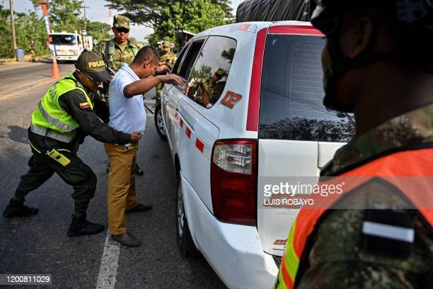 Colombian police officer frisks a driver at a checkpoint in rural area of Jamundi, Valle del Cauca, Colombia on February 14 during a nationwide...