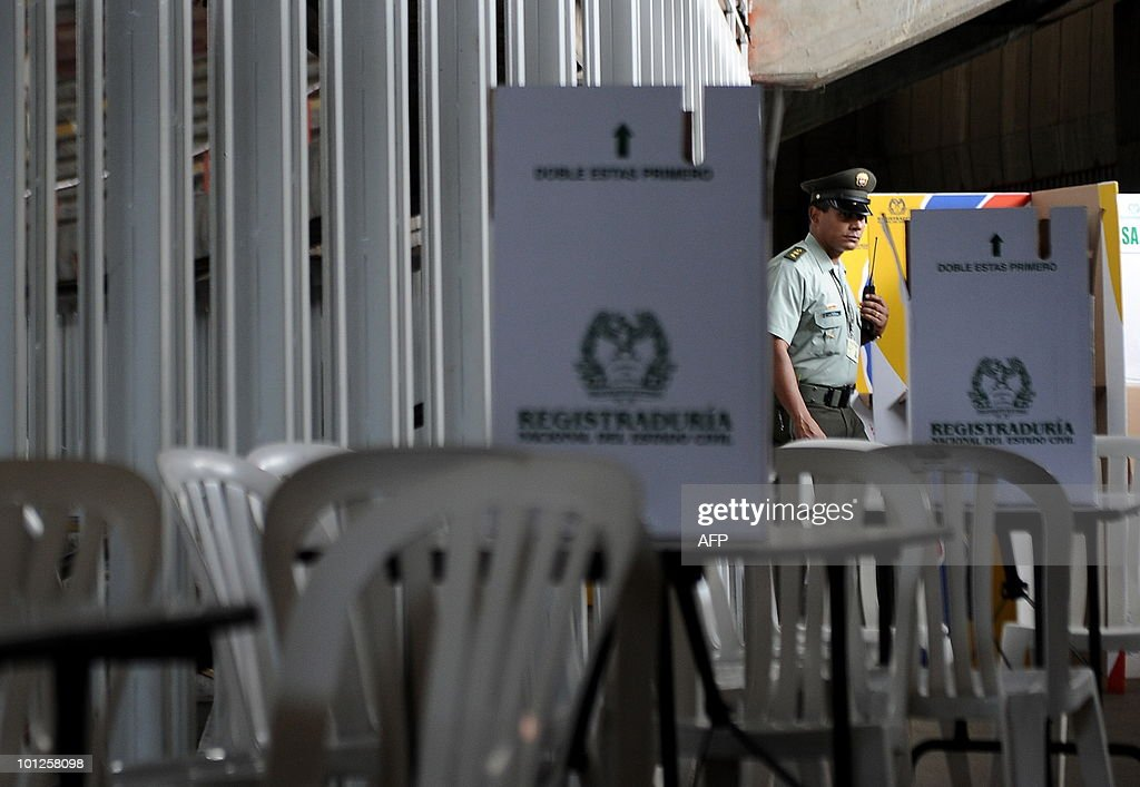 A Colombian police officer keeps watch over electoral stuff at a polling center in Cali, Valle del Cauca departament, Colombia, on May 29, 2010. Colombia will hold presidential elections next May 30, and according to polls, a run-off election between Antanas Mockus for the Green Party and Juan Manuel Santos for the ruling National Unity Party, will take place on June 20. AFP PHOTO/Luis ROBAYO